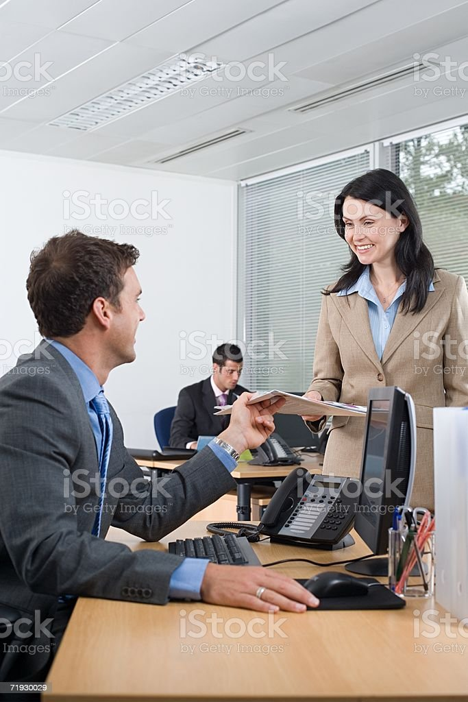 Businesspeople exchanging a brochure royalty-free stock photo