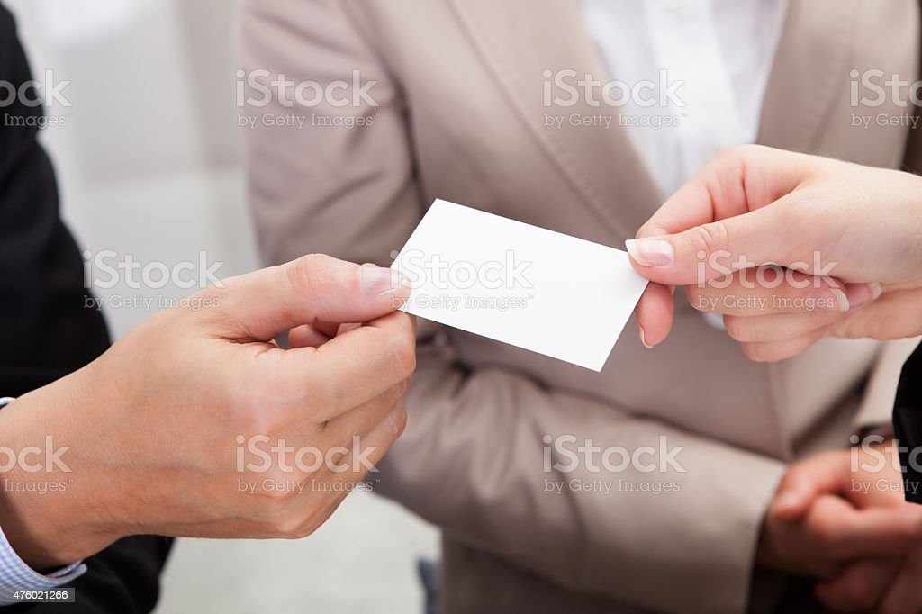 Businesspeople exchanging cards over coffee stock photo