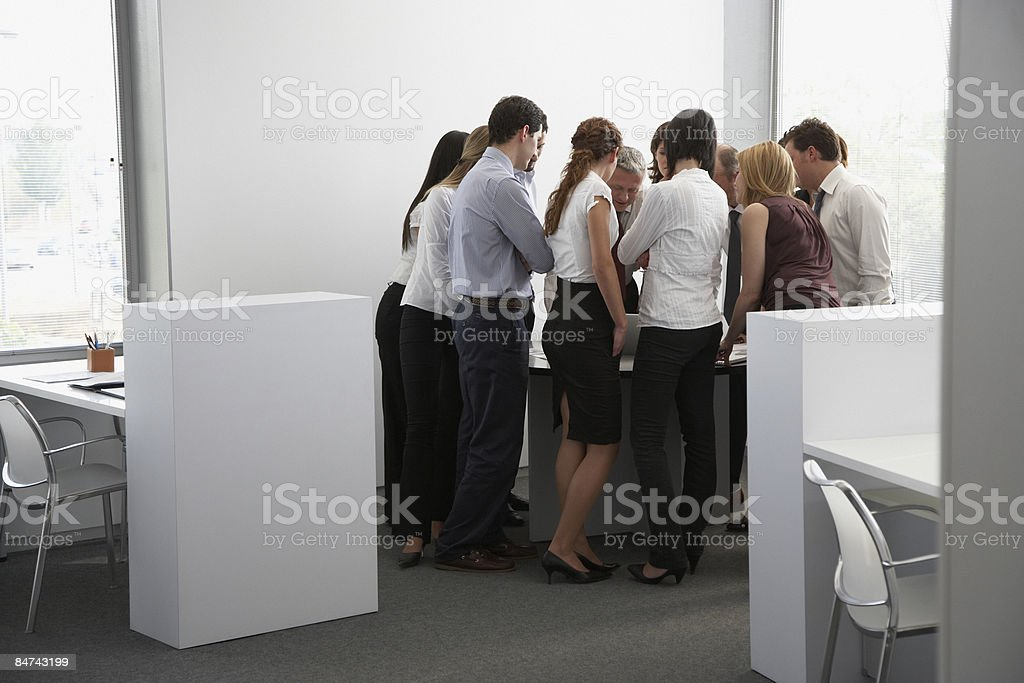 Businesspeople gathering around office desk royalty-free stock photo