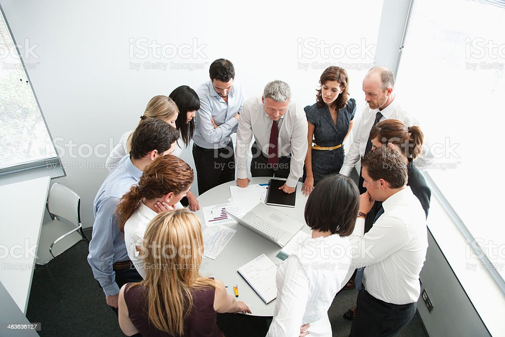 Businesspeople gathering around office table stock photo