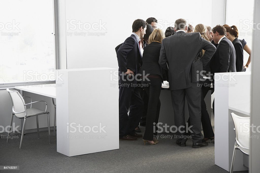 Businesspeople gathering in corner of office royalty-free stock photo