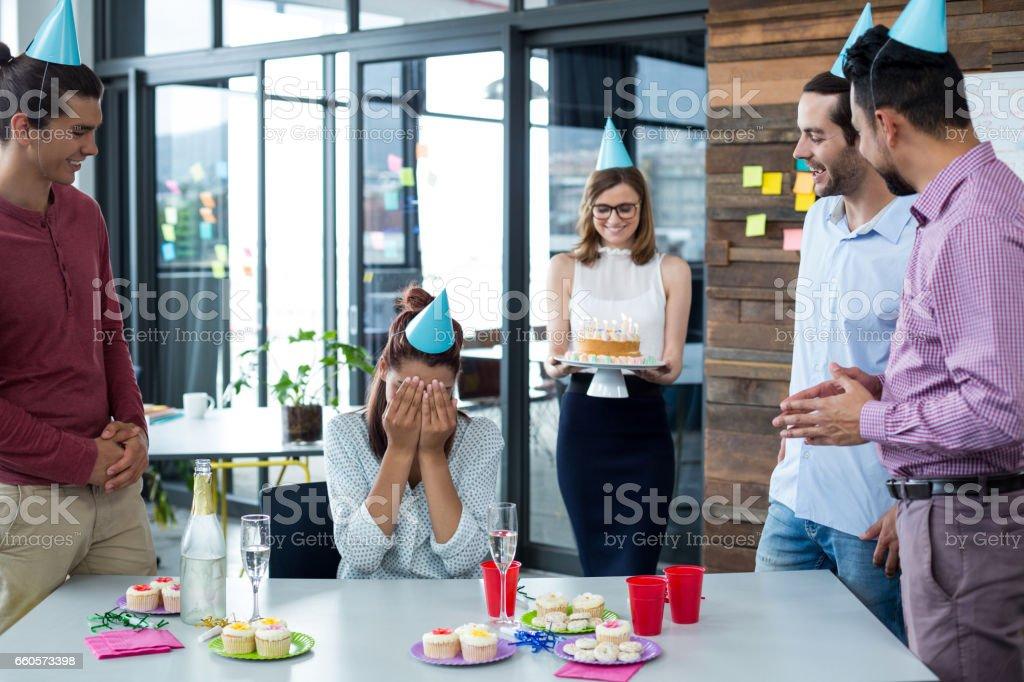 Les gens d'affaires donnant la fête d'anniversaire surprise à une collègue - Photo