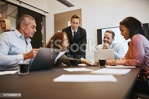 istock Businesspeople going through documents together in an office boardroom 1070696976