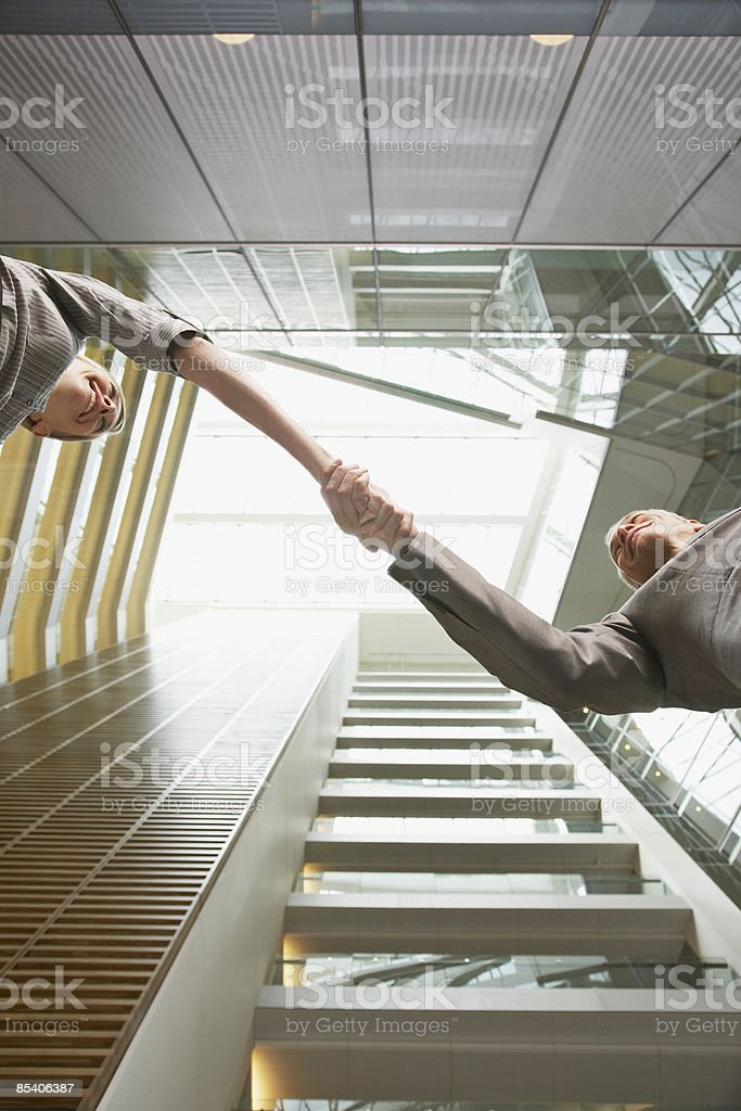 Businesspeople handshaking in building atrium royalty-free stock photo