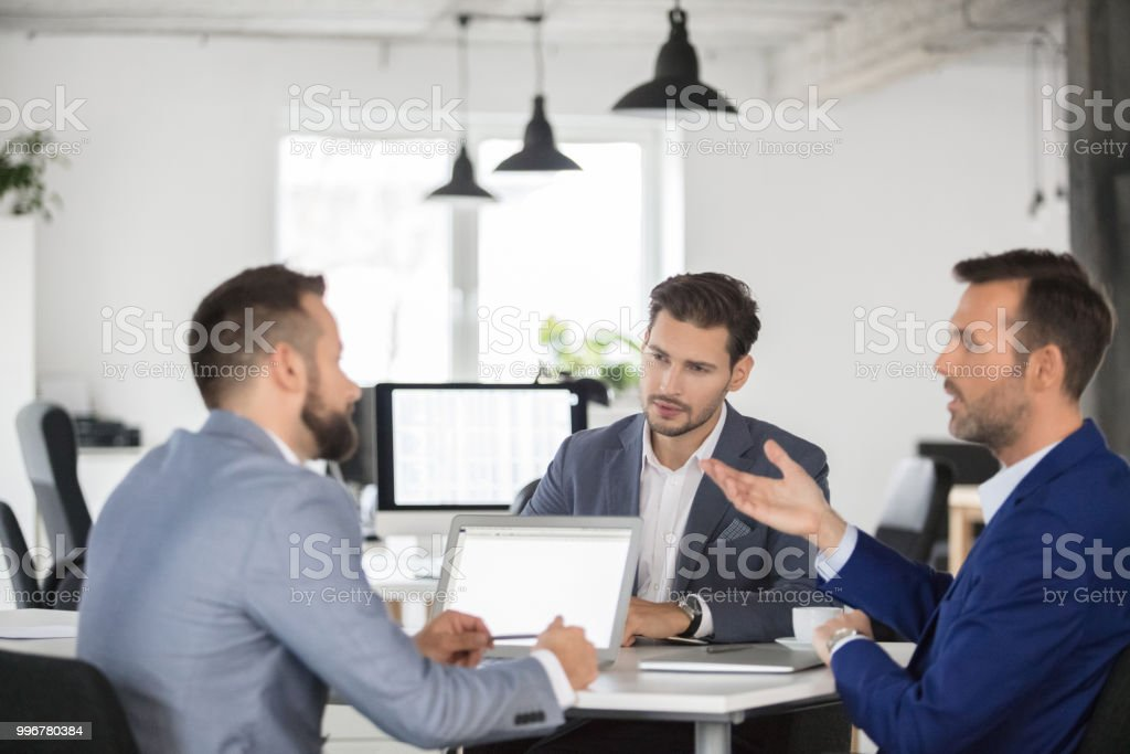 Businesspeople having a project meeting in office. Team of professionals having a discussion over new business plan. Businesspeople having a project meeting in office. Adult Stock Photo
