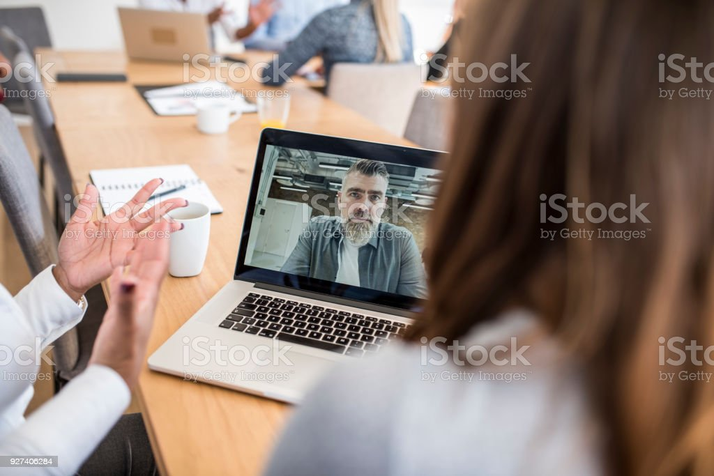Businesspeople having a video conference call with their boss stock photo