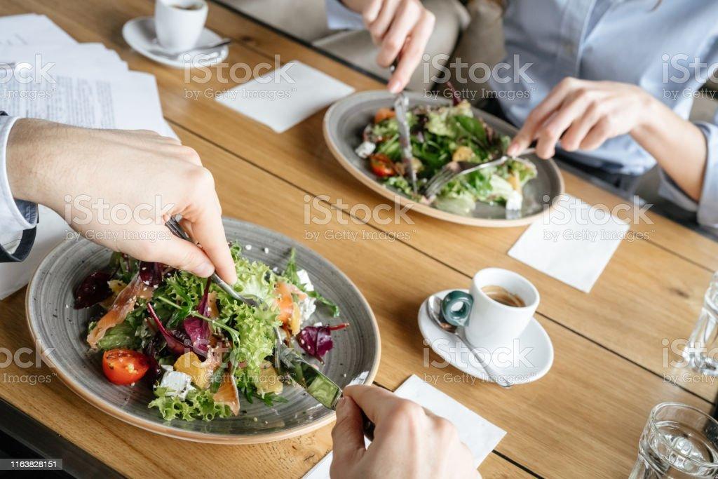 Företagare som har affärslunch på restaurang sittande äta sallad närbild - Royaltyfri Affärskvinna Bildbanksbilder