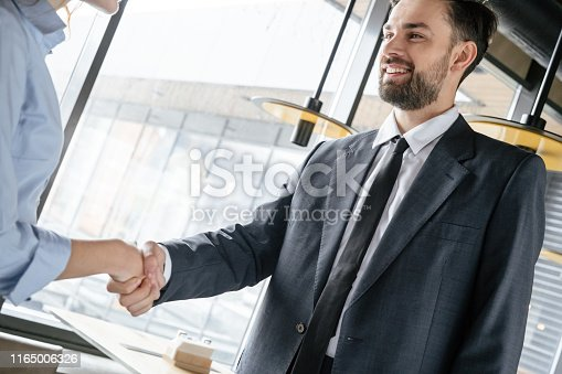Man and woman having business lunch at restaurant standing shaking hands businessman smiling friendly