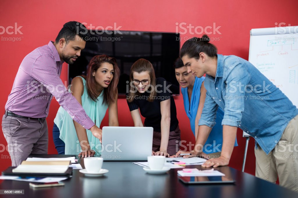 Businesspeople having discussion over laptop in office royalty-free stock photo