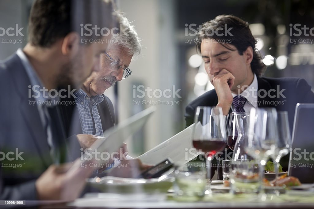 Businesspeople having lunch at restaurant and  studying paperwork stock photo