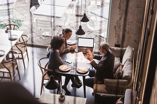 Two female collegues having business meeting in high end restaurant with senior client. Multi-ethnic group. High angle view