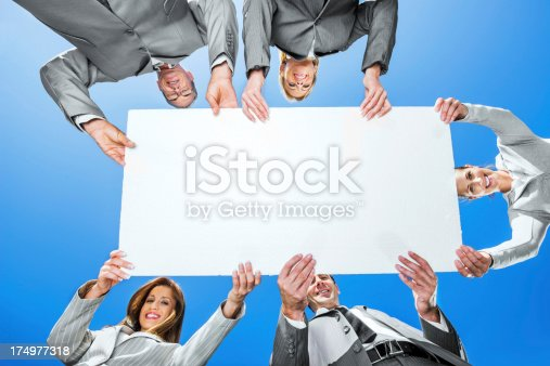 1048561866 istock photo Businesspeople holding a cardboard against the sky 174977318