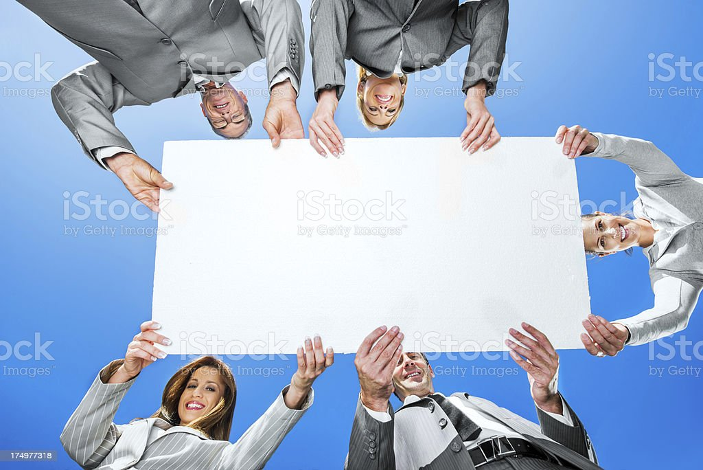 Businesspeople holding a cardboard against the sky stock photo