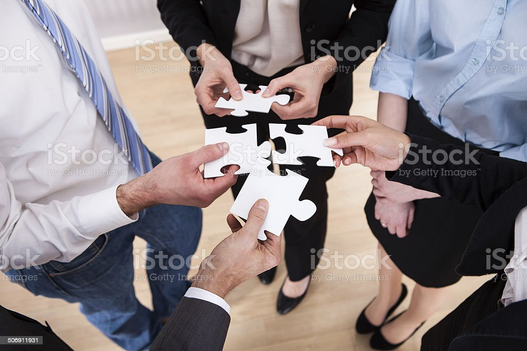 Businesspeople Holding Jigsaw Puzzle stock photo