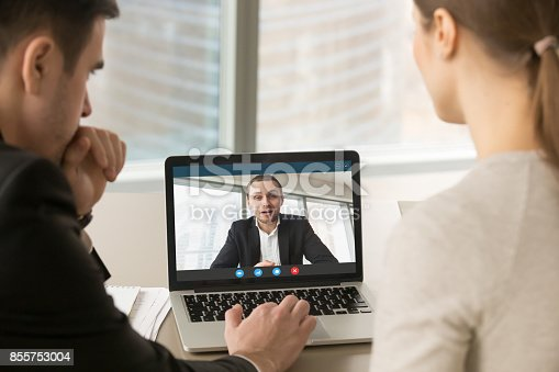 istock Businesspeople holding online meeting on laptop, making video ca 855753004