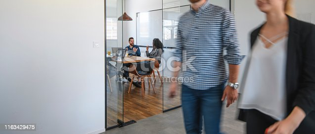 1163429625istockphoto Businesspeople in Conference Room and Colleagues Walking By 1163429475