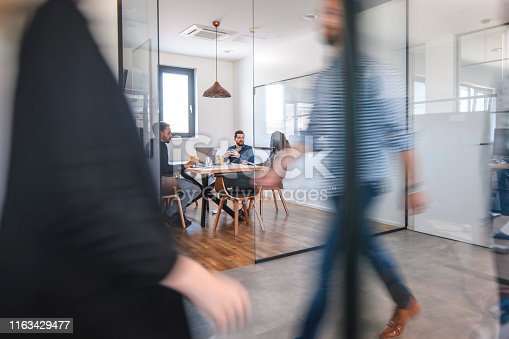 1163429625istockphoto Businesspeople in Conference Room and Colleagues Walking By 1163429477