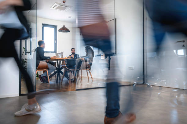 Businesspeople in Conference Room and Colleagues Walking By stock photo