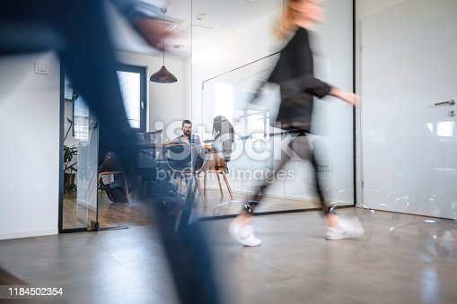 1163429625istockphoto Businesspeople in Conference Room and Colleagues Walking By 1184502354