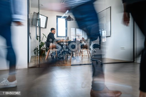 1163429625istockphoto Businesspeople in Conference Room and Colleagues Walking By 1184502362