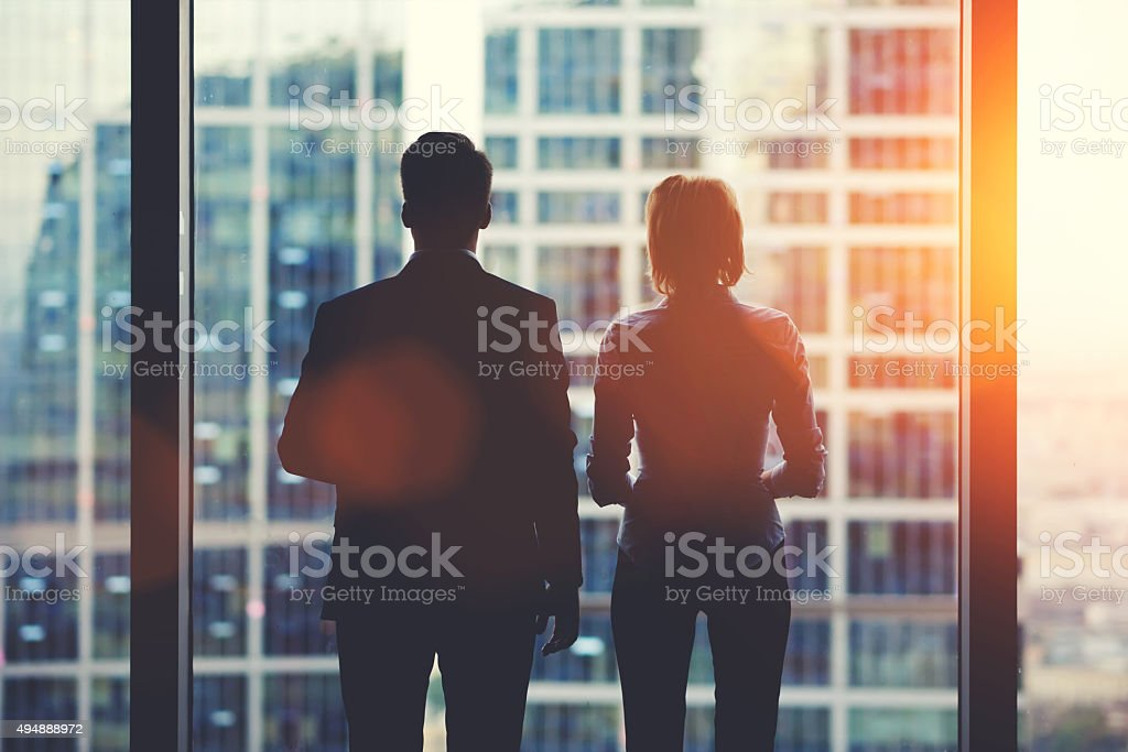 Businesspeople in fear or risk watching cityscape from skyscraper interior stock photo