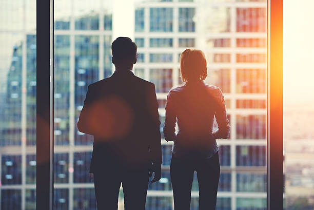 Businesspeople in fear or risk watching cityscape from skyscraper interior Back view silhouettes of two business partners looking thoughtfully out of a office window in situation of bankruptcy, high society stock pictures, royalty-free photos & images