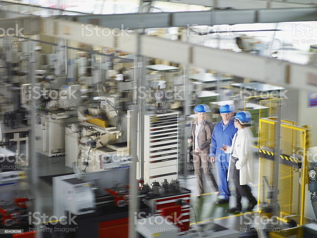 Businesspeople in hard-hats walking on factory floor royalty-free stock photo