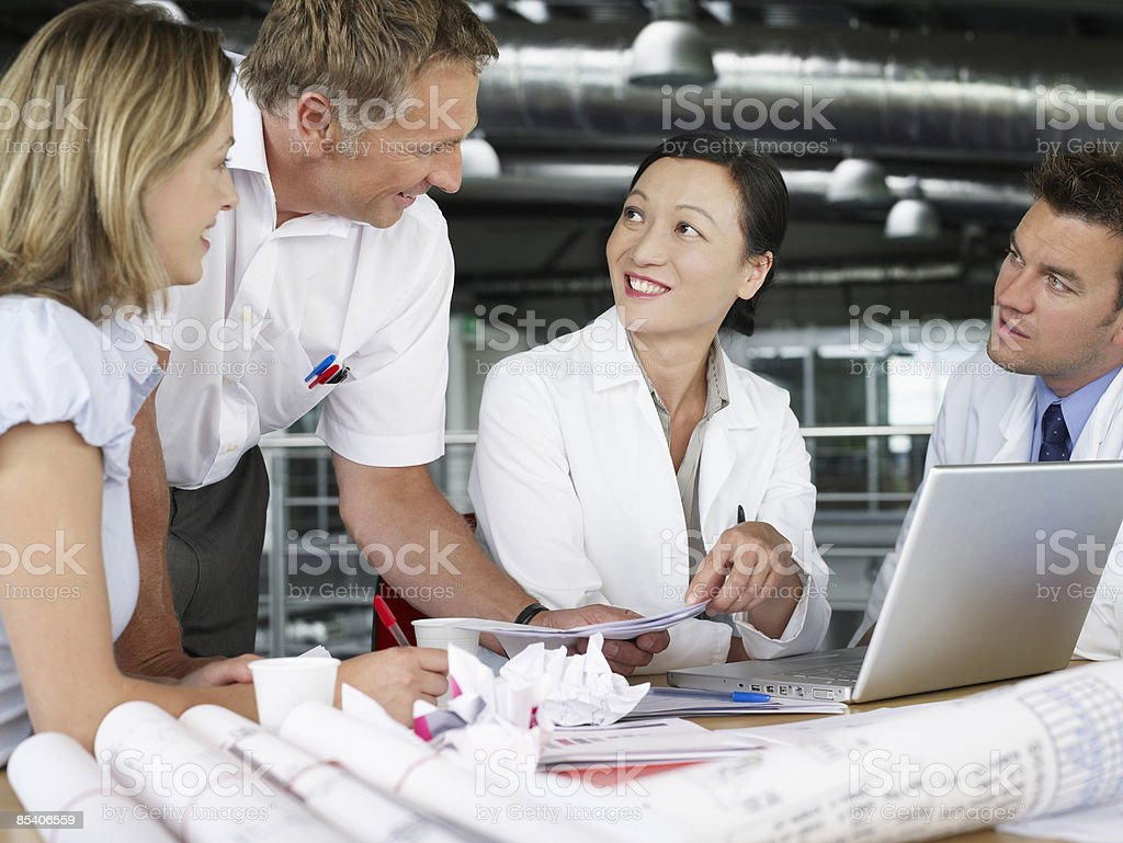 Businesspeople in meeting with blueprints royalty-free stock photo