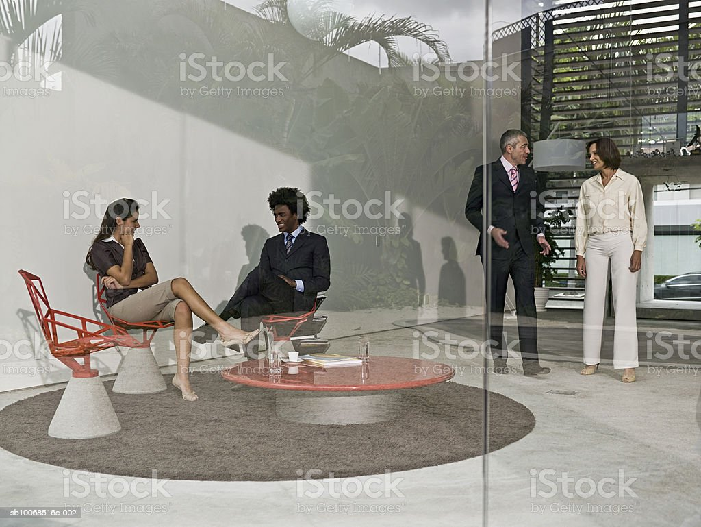 Businesspeople in office lobby talking royalty-free stock photo