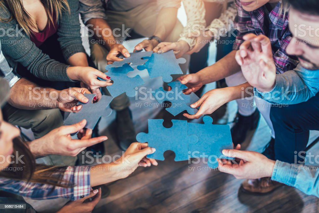 Businesspeople joining puzzle pieces in office stock photo