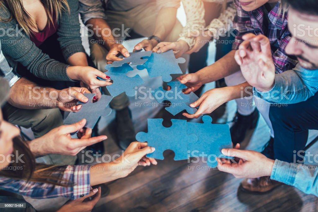 Empresarios unir piezas de rompecabezas en la oficina - foto de stock
