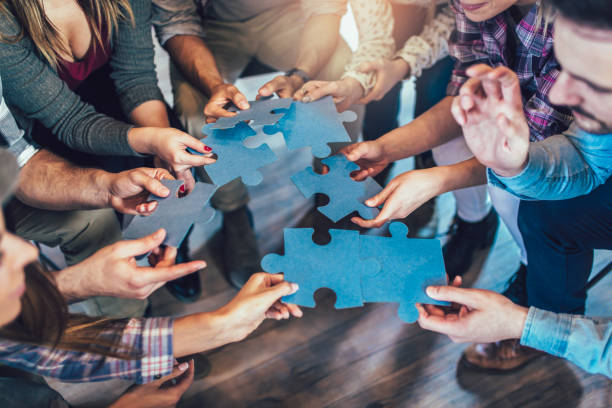 businesspeople joining puzzle pieces in office - puzzle foto e immagini stock