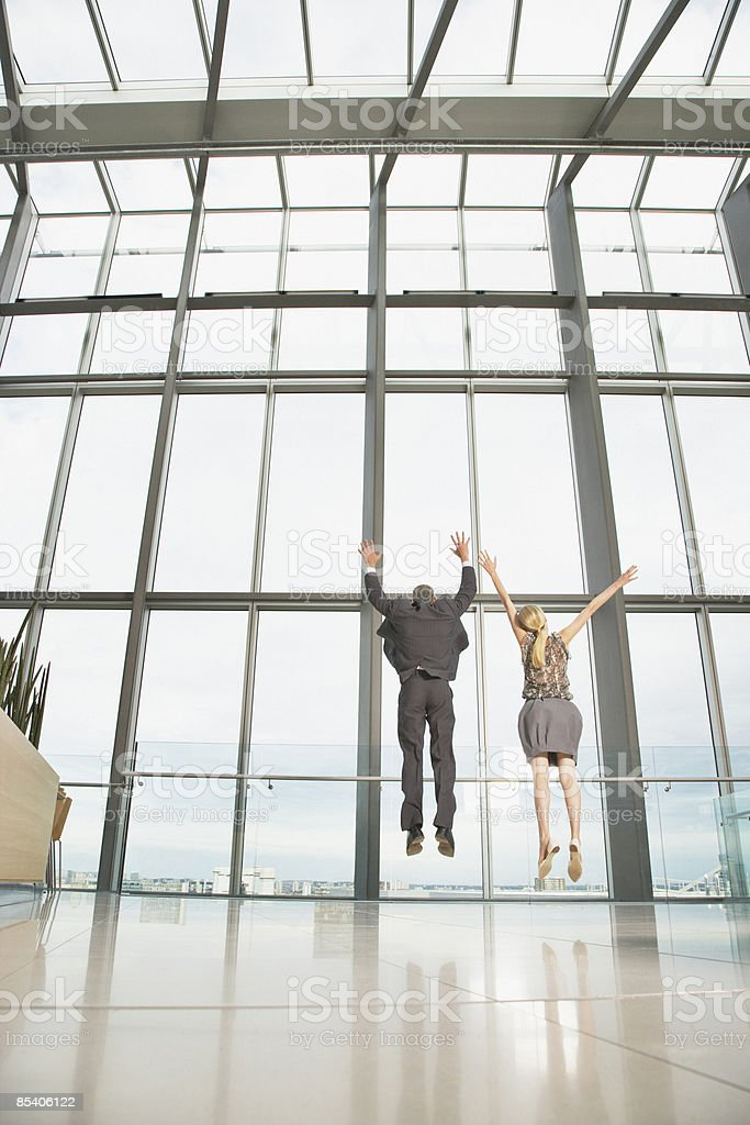 Businesspeople jumping in modern lobby royalty-free stock photo