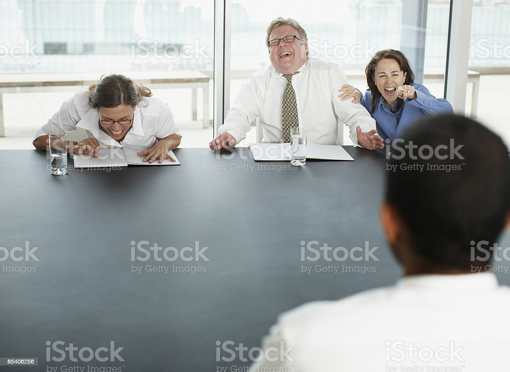 Businesspeople laughing at applicant in interview stock photo
