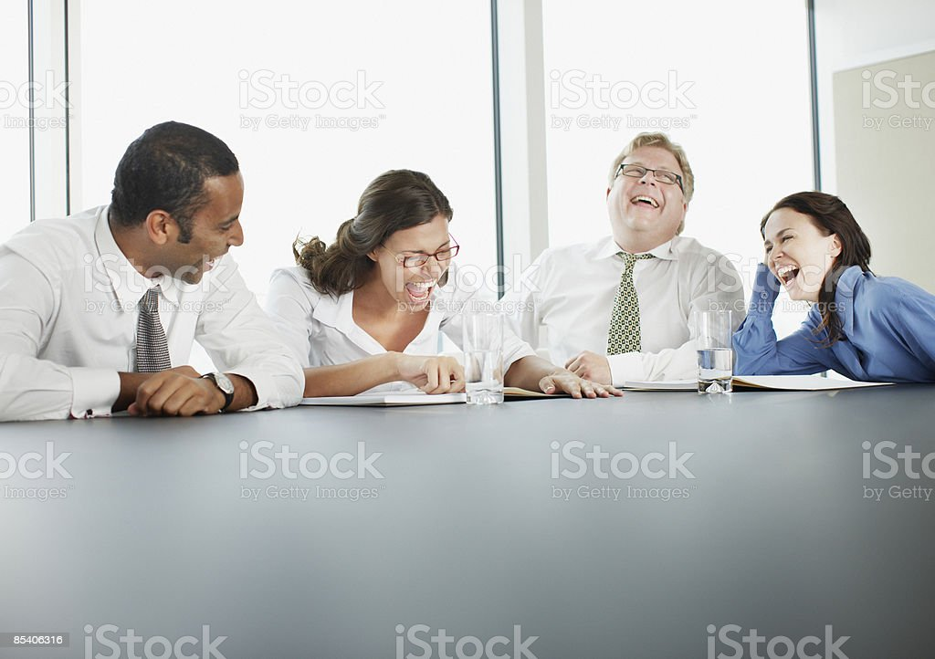 Businesspeople laughing in conference room royalty-free stock photo