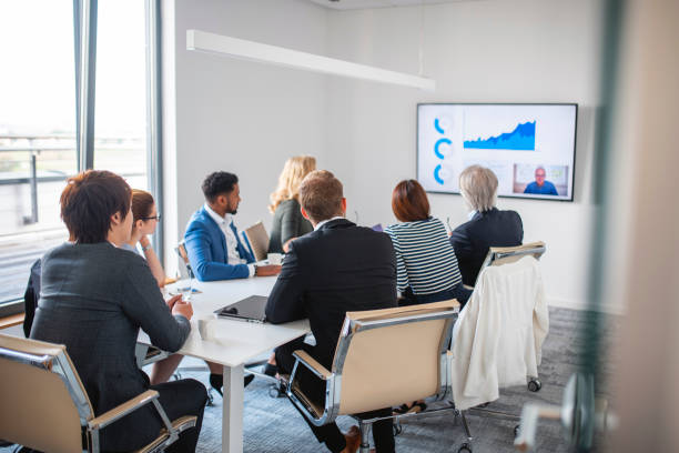 Businesspeople Listening to CEO on Video Conference stock photo