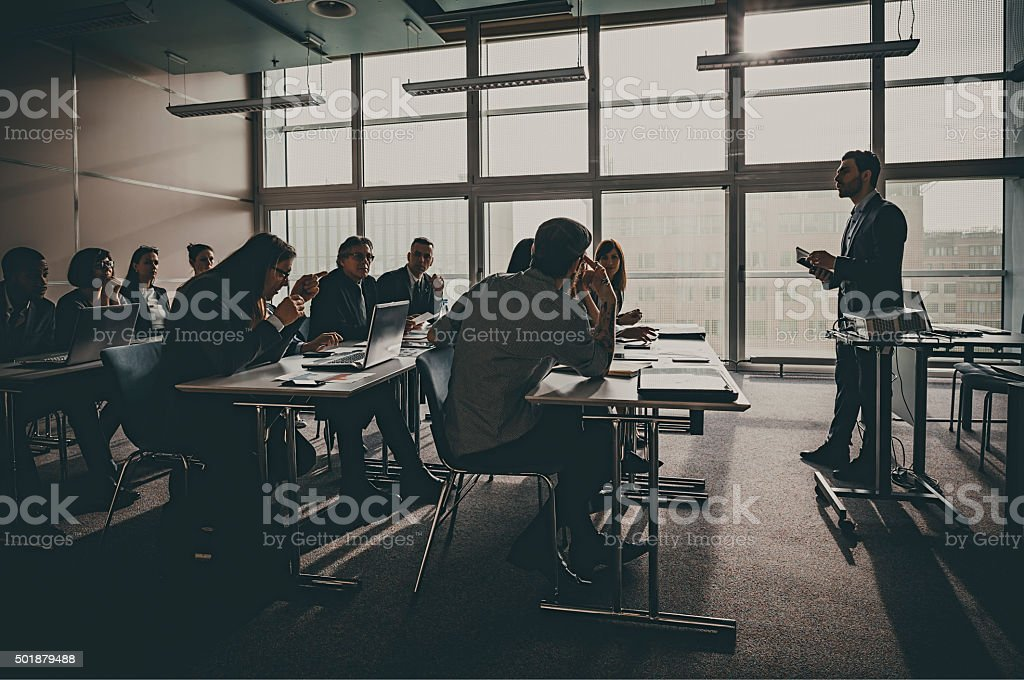 Businesspeople listening to presentation in office building stock photo