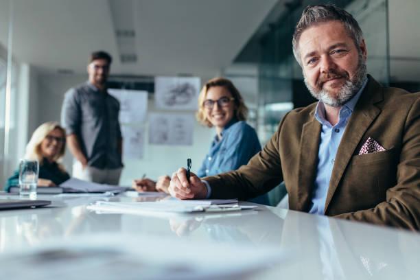 businesspeople looking at camera with smile - persona in secondo piano foto e immagini stock
