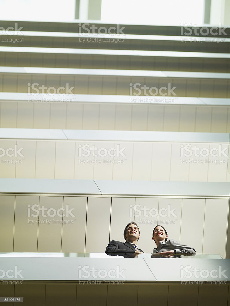 Businesspeople looking over balcony in atrium royalty-free stock photo
