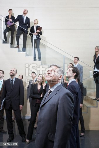 84743203 istock photo Businesspeople looking up in office lobby 84743239