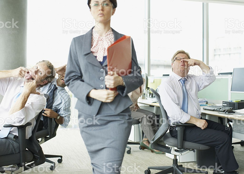 Businesspeople making face at boss in office royalty-free stock photo