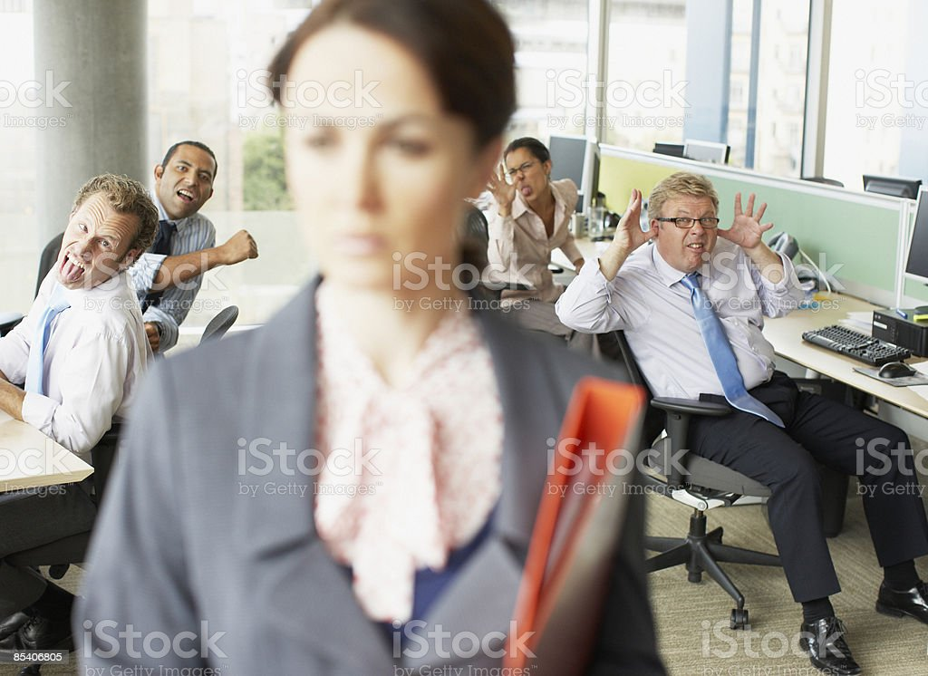 Businesspeople making face at boss in office stock photo