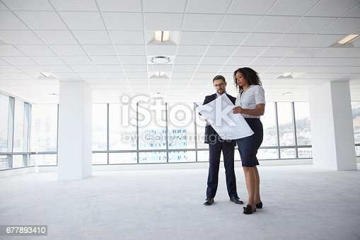 istock Businesspeople Meeting To Look At Plans In Empty Office 677893410
