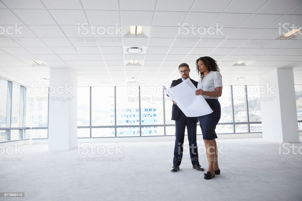 Businesspeople Meeting To Look At Plans In Empty Office stock photo