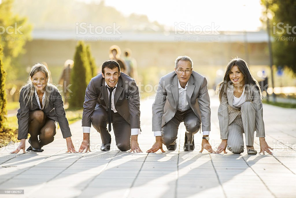 Businesspeople on a starting line, ready to run stock photo