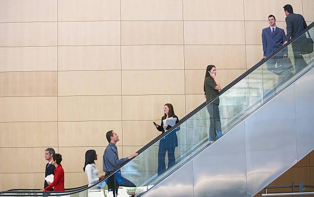 Businesspeople on escalator stock photo