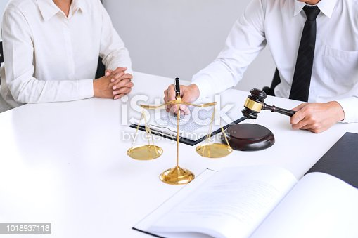 941906652 istock photo Businesspeople or lawyer having team meeting discussing agreement contract documents, judge gavel with Justice lawyers at law firm in background, Legal law, advice and justice concept 1018937118