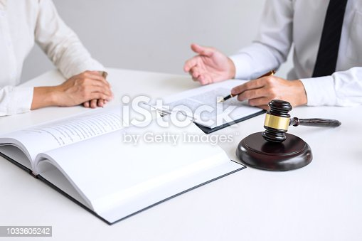 941906652 istock photo Businesspeople or lawyer having team meeting discussing agreement contract documents, judge gavel with Justice lawyers at law firm in background, Legal law, advice and justice concept 1033605242