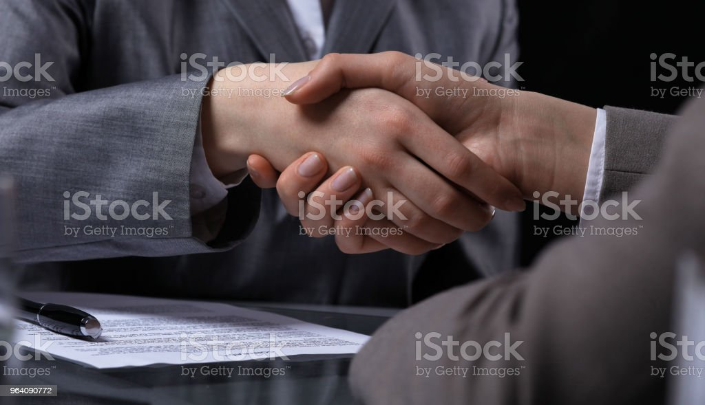 Businesspeople or lawyers shaking hands at meeting. Close-up of human hands at work. Signing contract concept. Low key lighting - Royalty-free Adult Stock Photo