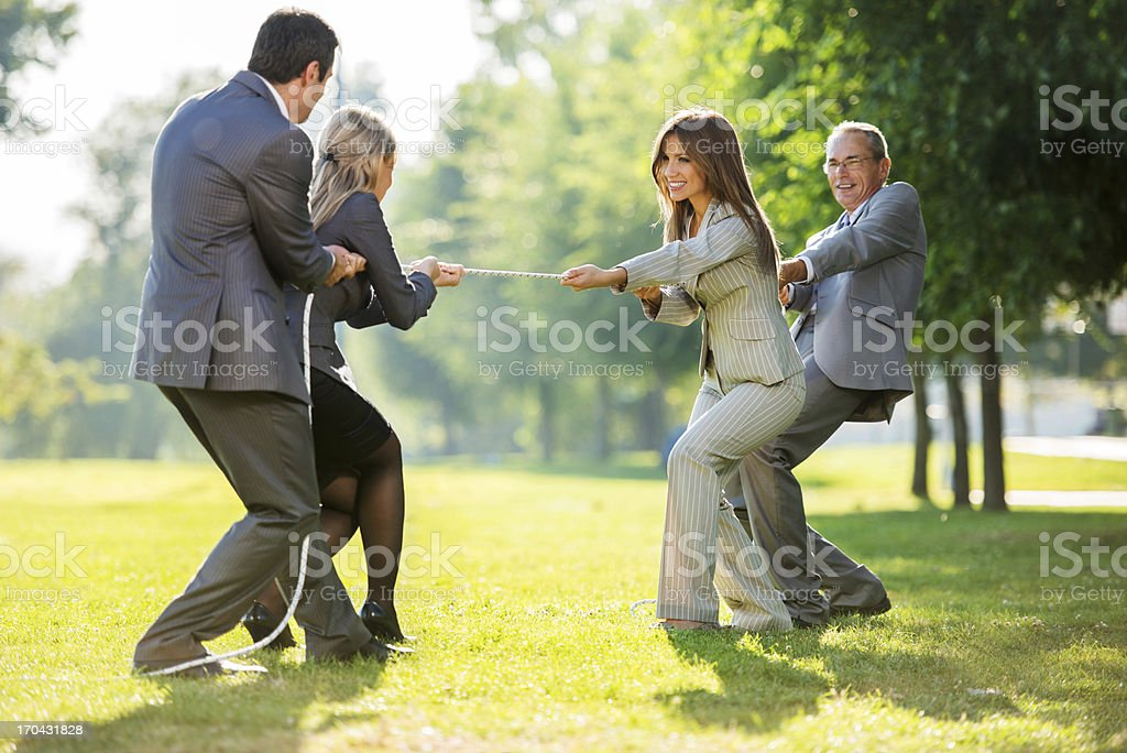 Businesspeople playing tug of war outdoors. royalty-free stock photo